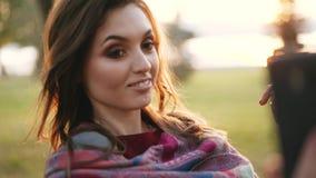 Muchacha feliz que peina el pelo en el smartphone en un parque del otoño almacen de metraje de vídeo