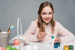 Muchacha feliz que pinta el huevo de Pascua y que sonríe en la cámara Imagen de archivo libre de regalías