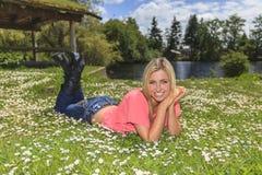 Muchacha feliz que pone en la hierba Imagenes de archivo