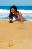 Muchacha feliz que pone en la playa Imágenes de archivo libres de regalías