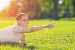 Muchacha feliz que pone en prado Foto de archivo