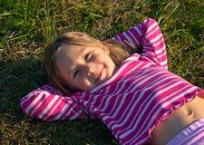 Muchacha feliz que pone en una hierba Fotos de archivo libres de regalías