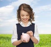 Muchacha feliz que pone la moneda en la hucha Imagenes de archivo