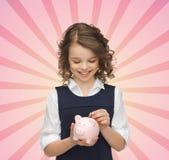 Muchacha feliz que pone la moneda en la hucha Imagen de archivo