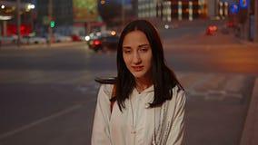 Muchacha feliz que presenta en la calle delante del tráfico de ciudad borroso en la noche metrajes