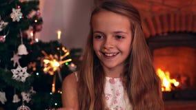 Muchacha feliz que ríe y que agita una bengala de la Navidad almacen de metraje de vídeo