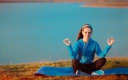 Muchacha feliz que reflexiona sobre la estera de la yoga en naturaleza Foto de archivo