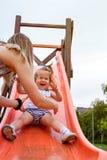 Muchacha feliz que resbala abajo en diapositiva Foto de archivo