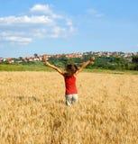 Muchacha feliz que salta en campo de trigo Foto de archivo libre de regalías