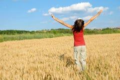 Muchacha feliz que salta en campo de trigo Fotografía de archivo