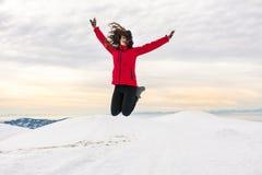 Muchacha feliz que salta en el top nevado de la montaña Imagen de archivo libre de regalías
