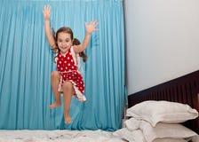 Muchacha feliz que salta en la cama Imagenes de archivo