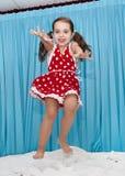 Muchacha feliz que salta en la cama Fotografía de archivo