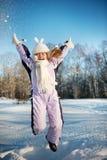 Muchacha feliz que salta en la nieve Foto de archivo