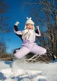 Muchacha feliz que salta en la nieve Imagen de archivo libre de regalías