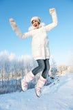 Muchacha feliz que salta en la nieve Fotografía de archivo libre de regalías