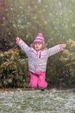 Muchacha feliz que salta en la nieve Foto de archivo libre de regalías