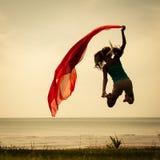 Muchacha feliz que salta en la playa Fotos de archivo