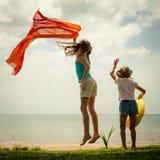Muchacha feliz que salta en la playa Foto de archivo