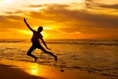 Muchacha feliz que salta en la playa Imágenes de archivo libres de regalías