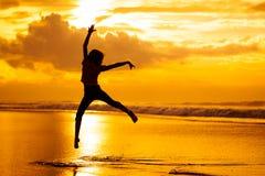 Muchacha feliz que salta en la playa Imagenes de archivo