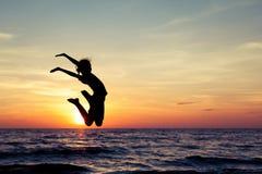 Muchacha feliz que salta en la playa Foto de archivo libre de regalías