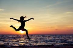 Muchacha feliz que salta en la playa Imagen de archivo