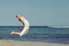 Muchacha feliz que salta en la playa Imagen de archivo libre de regalías