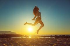 Muchacha feliz que salta en la playa contra puesta del sol hermosa Fotografía de archivo libre de regalías