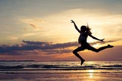 Muchacha feliz que salta en la playa en el tiempo de la puesta del sol Fotografía de archivo libre de regalías