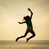 Muchacha feliz que salta en la playa en el tiempo del día Imágenes de archivo libres de regalías