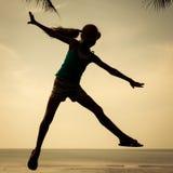 Muchacha feliz que salta en la playa en el tiempo del día Imagen de archivo