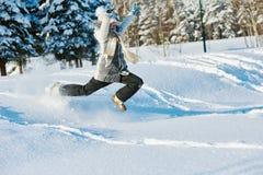 Muchacha feliz que salta en nieve en invierno Imágenes de archivo libres de regalías