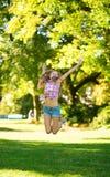 Muchacha feliz que salta en parque Fotografía de archivo libre de regalías