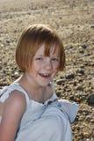 Muchacha feliz que se agacha en la playa Foto de archivo