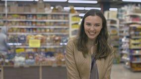 Muchacha feliz que se coloca en el supermercado Imagen de archivo libre de regalías