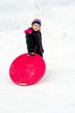 Muchacha feliz que se coloca en la nieve con un trineo del platillo Imagen de archivo
