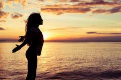 Muchacha feliz que se coloca en la playa Foto de archivo