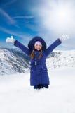 Muchacha feliz que se coloca en nieve Fotos de archivo