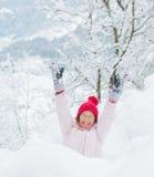 Muchacha feliz que se divierte en día de invierno que nieva. Fotografía de archivo