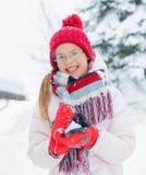 Muchacha feliz que se divierte en día de invierno que nieva. Foto de archivo