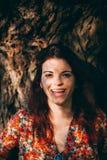 Muchacha feliz que se inclina contra un árbol Foto de archivo libre de regalías