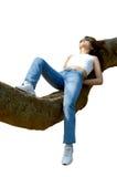 Muchacha feliz que se relaja al aire libre en la ramificación de árbol aislada Foto de archivo