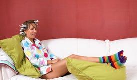 Muchacha feliz que se relaja en el sofá Imagen de archivo libre de regalías