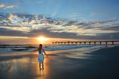Muchacha feliz que se relaja en la playa hermosa en la salida del sol Foto de archivo libre de regalías