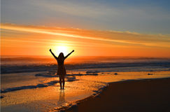 Muchacha feliz que se relaja en la salida del sol en la playa Imágenes de archivo libres de regalías