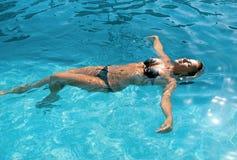 Muchacha feliz que se relaja en piscina fotografía de archivo