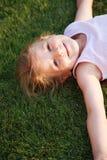 Muchacha feliz que se relaja en una hierba Foto de archivo