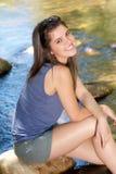 Muchacha feliz que se sienta al lado de corriente con los pies en agua Foto de archivo