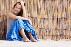 Muchacha feliz que se sienta cerca de la pared de bambú Foto de archivo